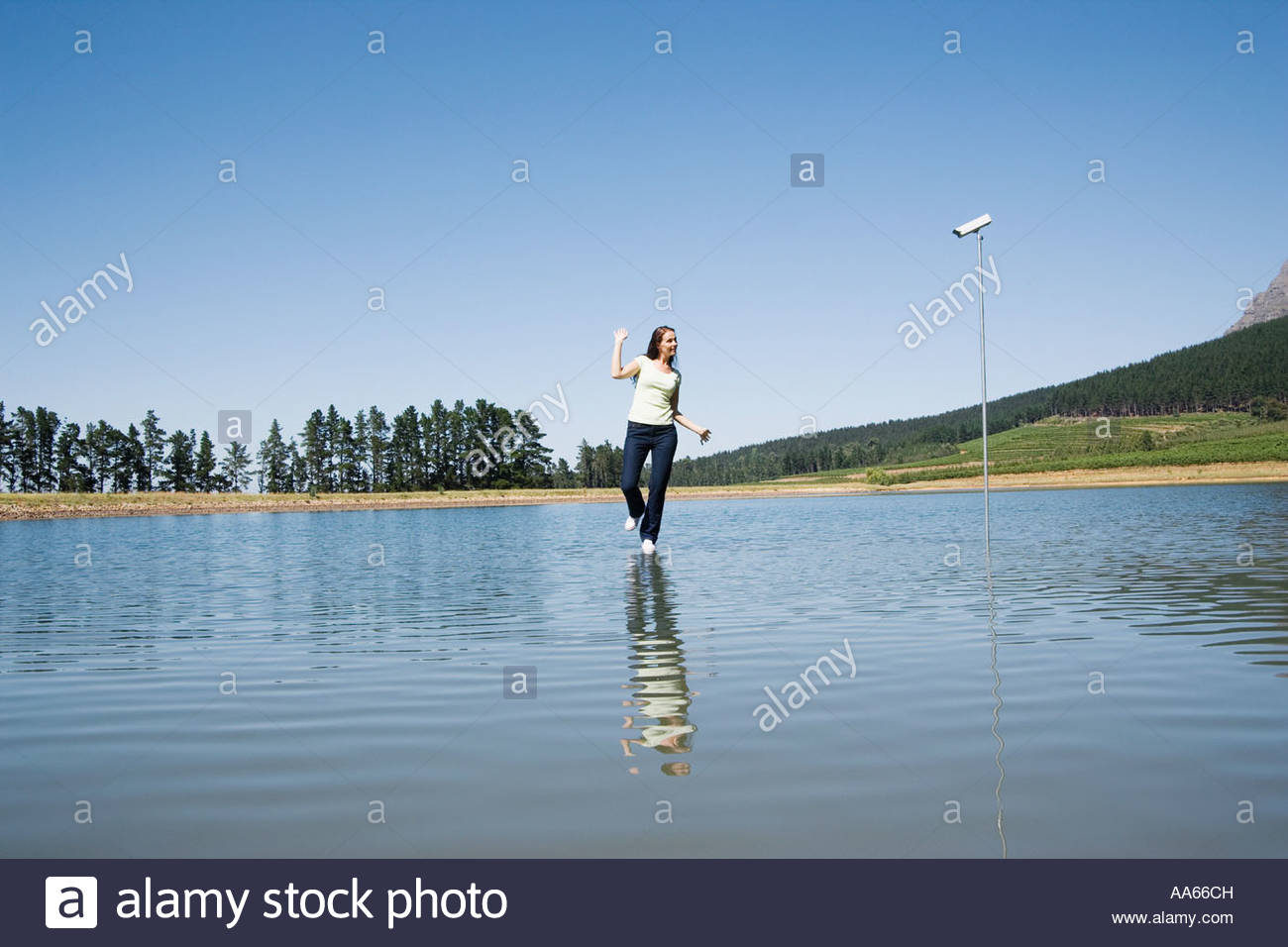 Woman dancing on water with surveillance camera and trees - Stock Image
