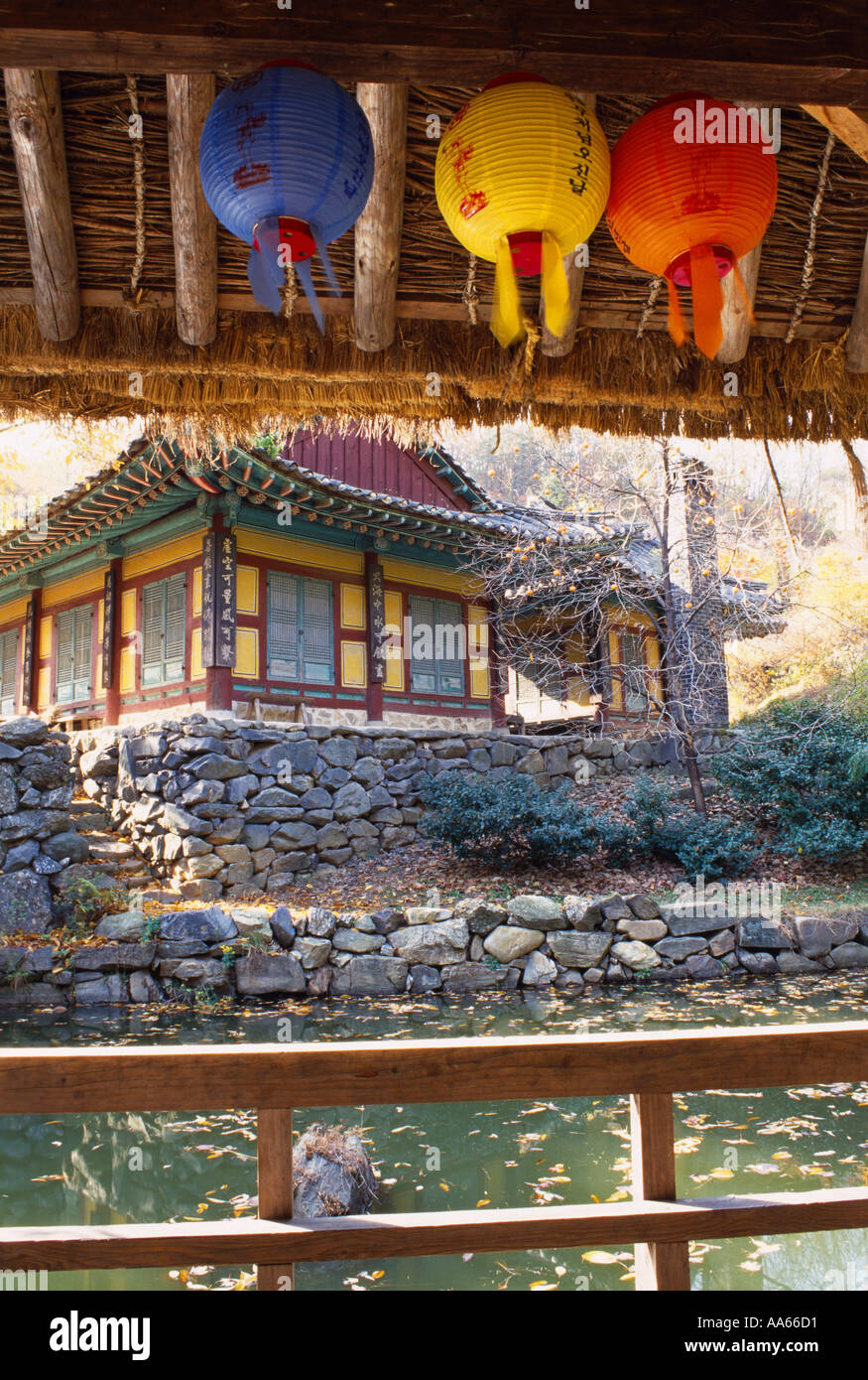 View of temple in Korea across lake with coloured paper lantern in front Hanguk Minsok Chon Gyeonggi do - Stock Image