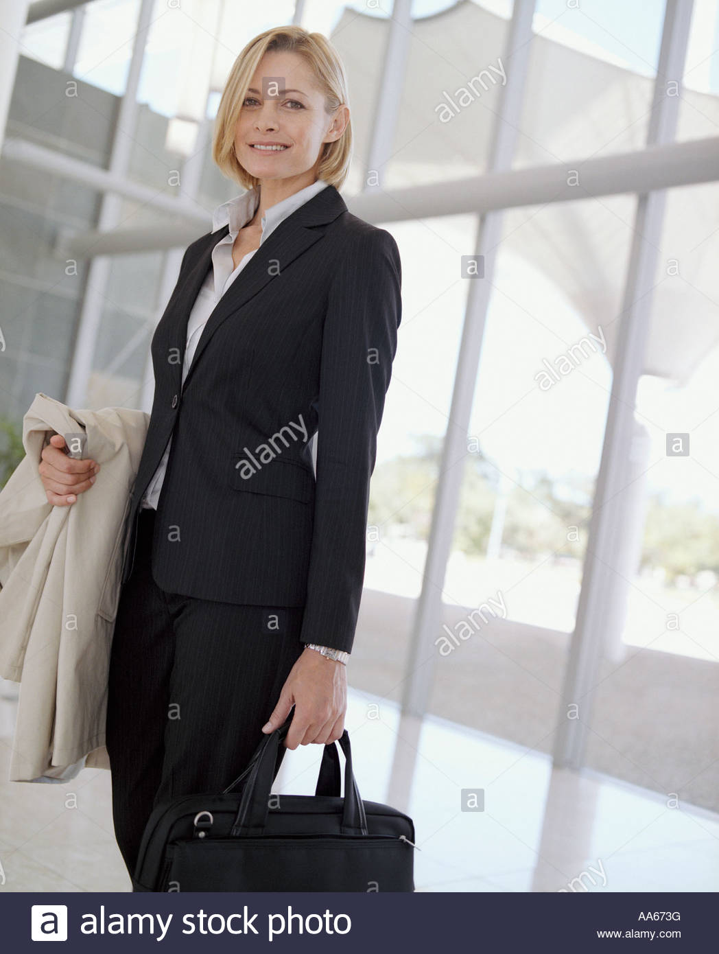 Businesswoman with briefcase and overcoat - Stock Image