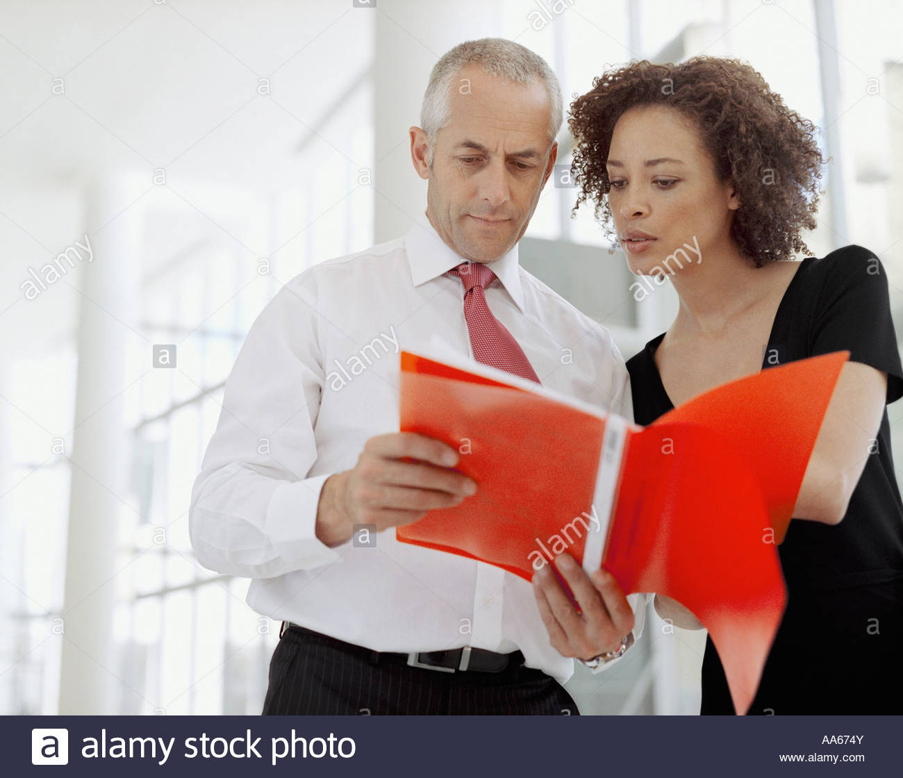 Businessman and businesswoman with document - Stock Image