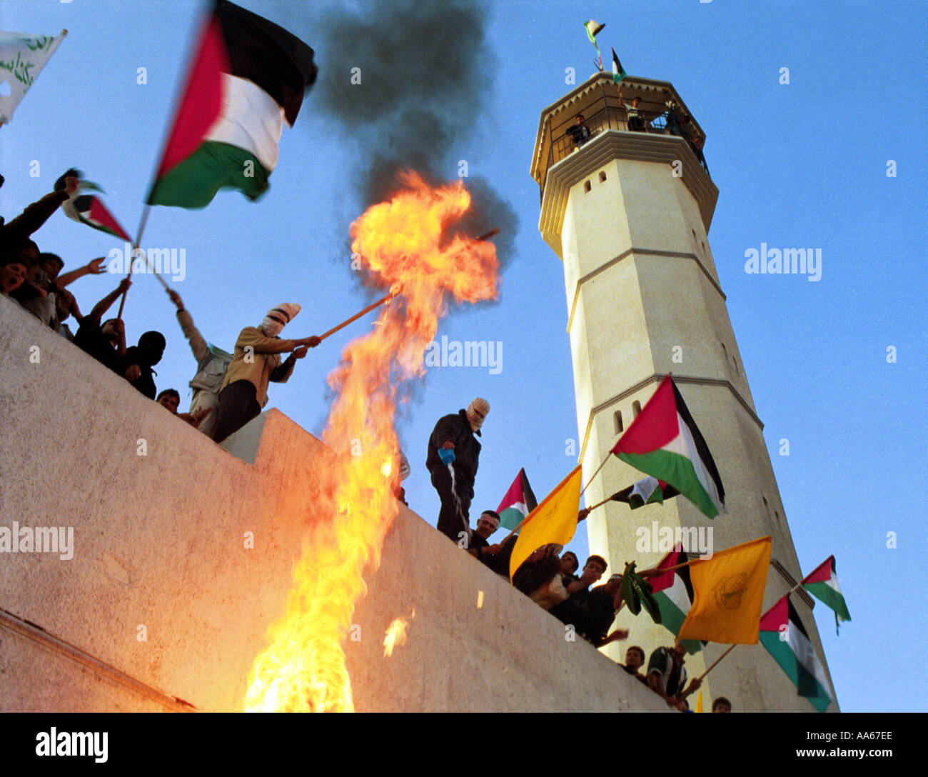 Armed and masked Palestinians burn Israeli flags at the funeral for 13 year old Eyad Shaath Tuesday October 23 2000 - Stock Image