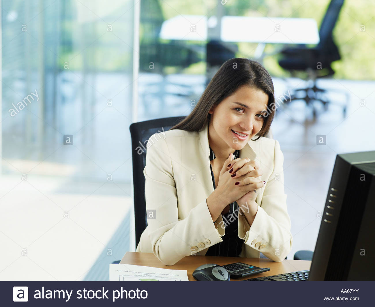 Woman in office working on her personal computer - Stock Image