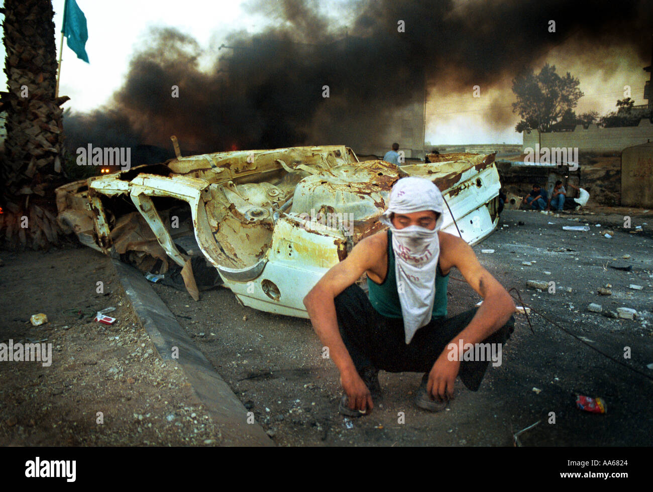A Palestinian hides behind a burning car and tire and tries to catch his breath after Israeli soldiers fired tear - Stock Image