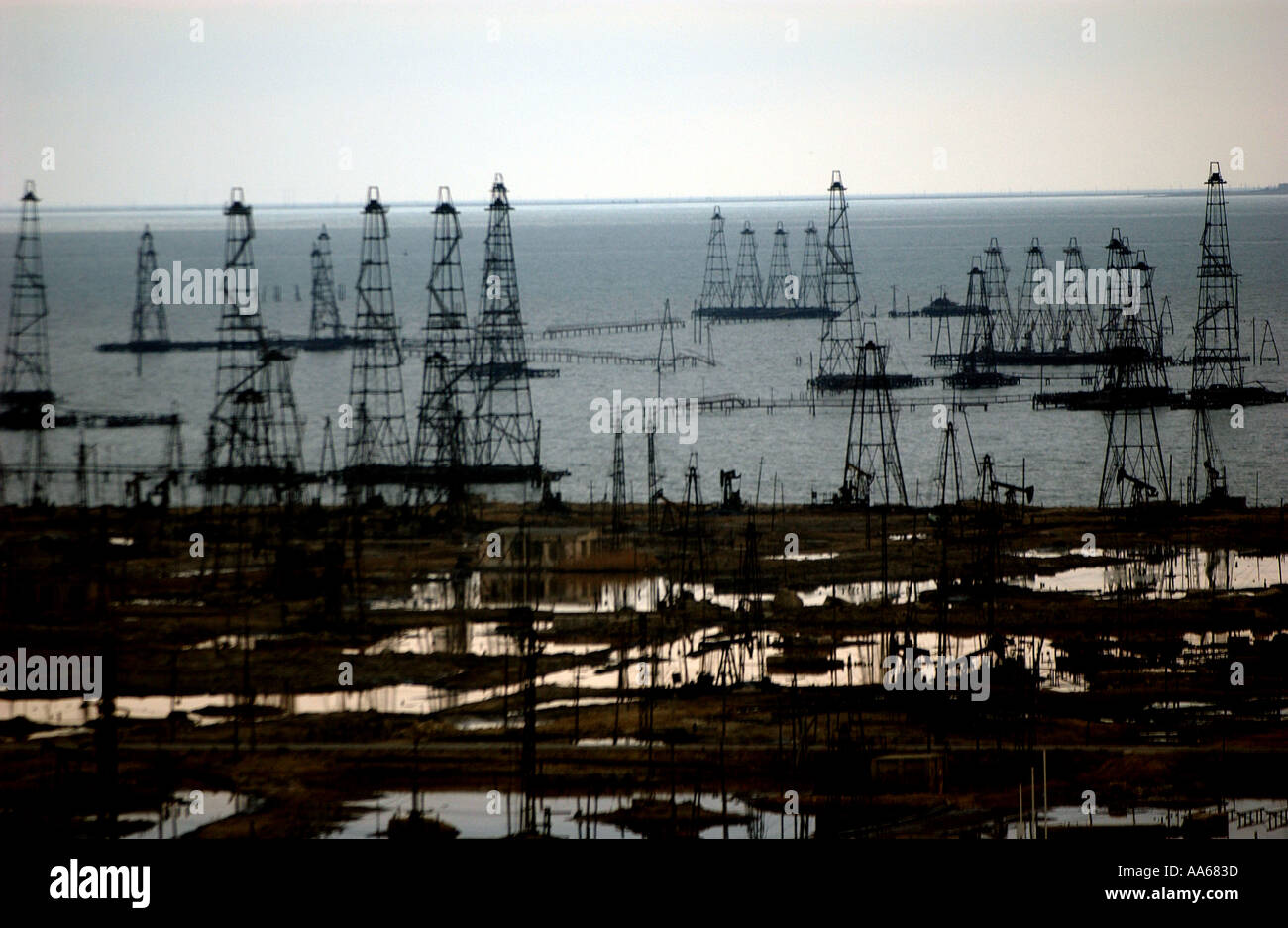 Ancient oil wells sit unused in a field in the Caspian Sea near Baku Azerbaijan in January 2003 Today life in Azerbaijan is - Stock Image