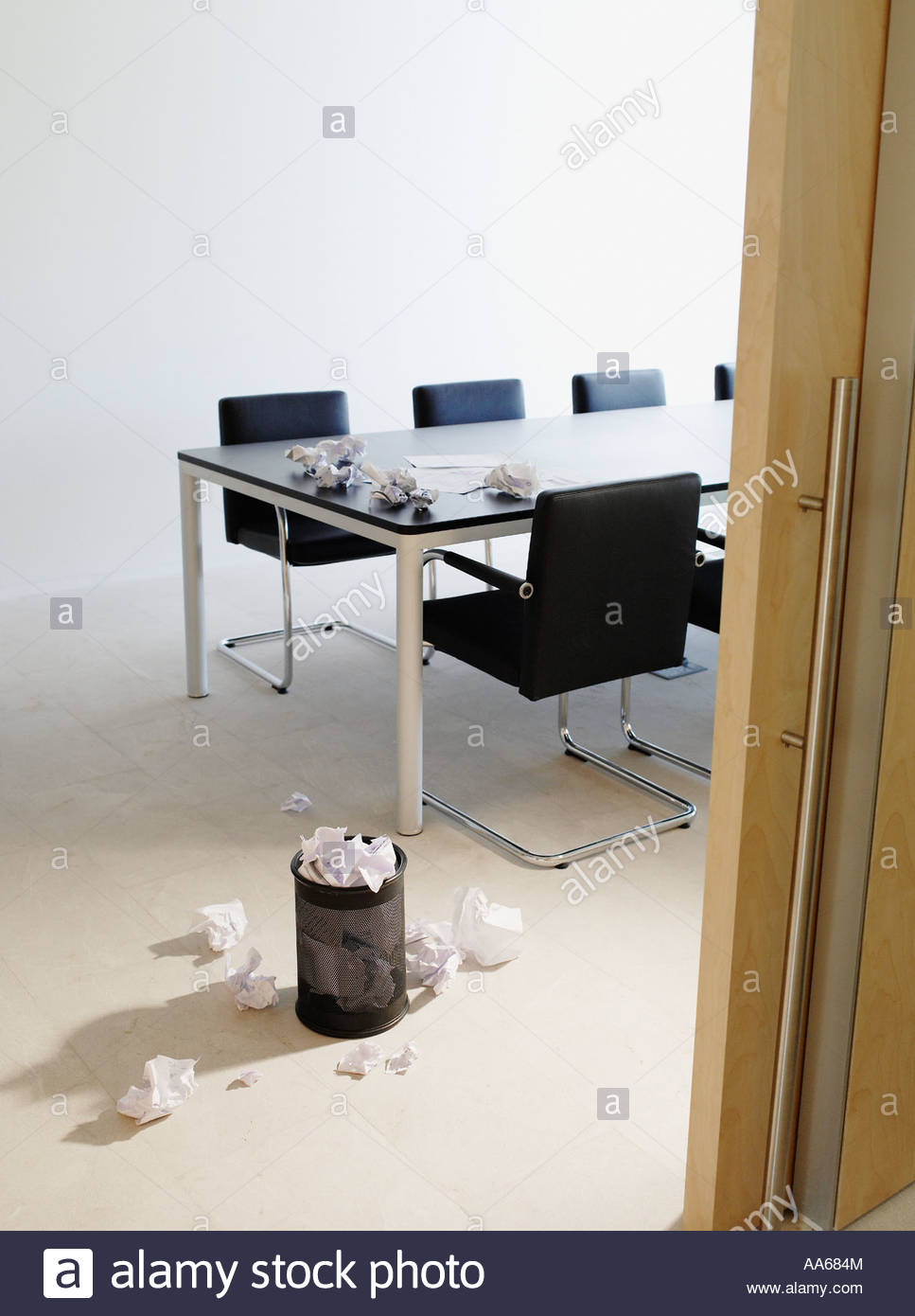 Empty boardroom littered with crumpled papers - Stock Image