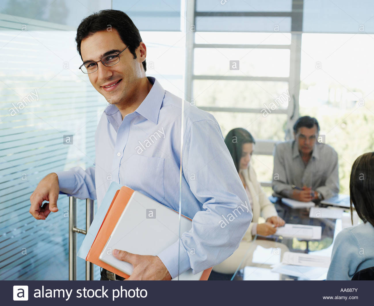 Male office worker holding papers while colleagues meet in background - Stock Image