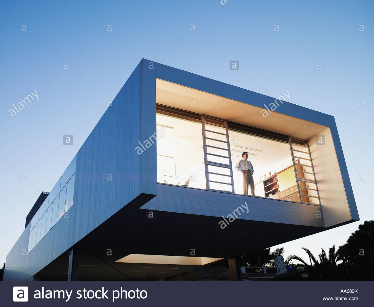 Exterior of a modern office building with man looking out window - Stock Image