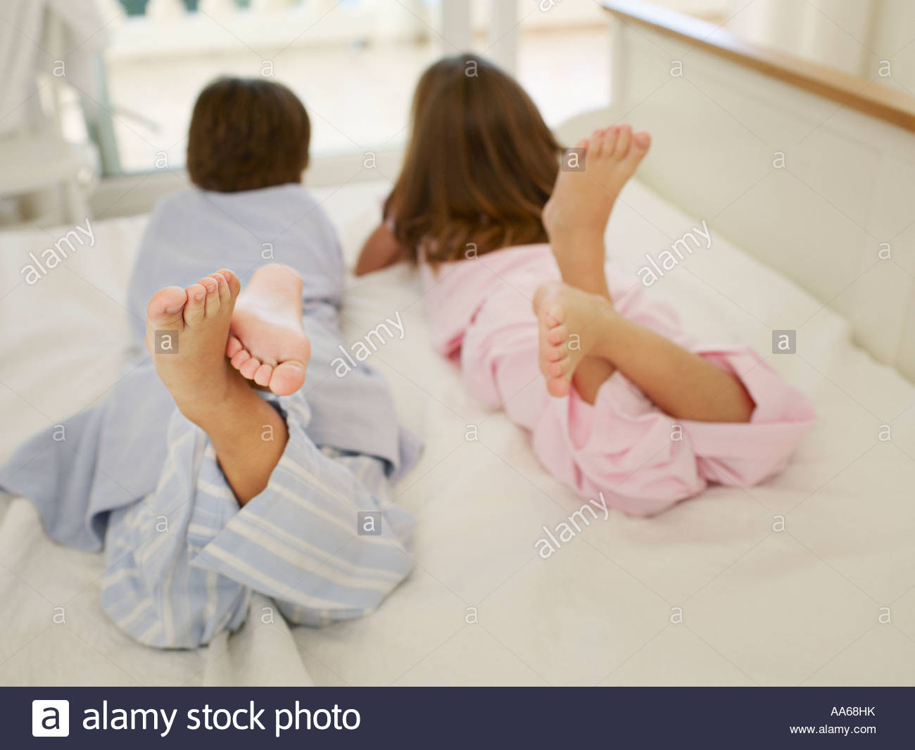 Young brother and sister on a bed lying on their stomachs - Stock Image