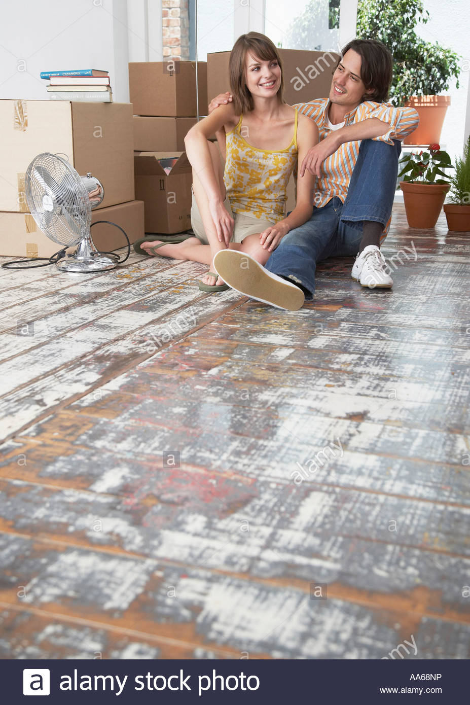 Man and woman sitting on hardwood floor with cardboard boxes and fan - Stock Image