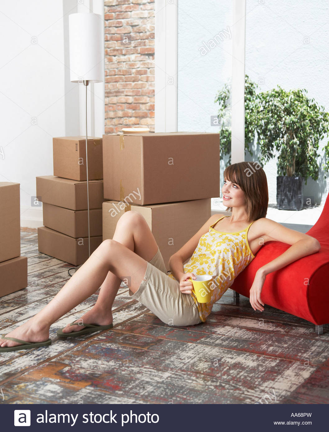 Woman sitting on hardwood floor with mug and cardboard boxes smiling - Stock Image