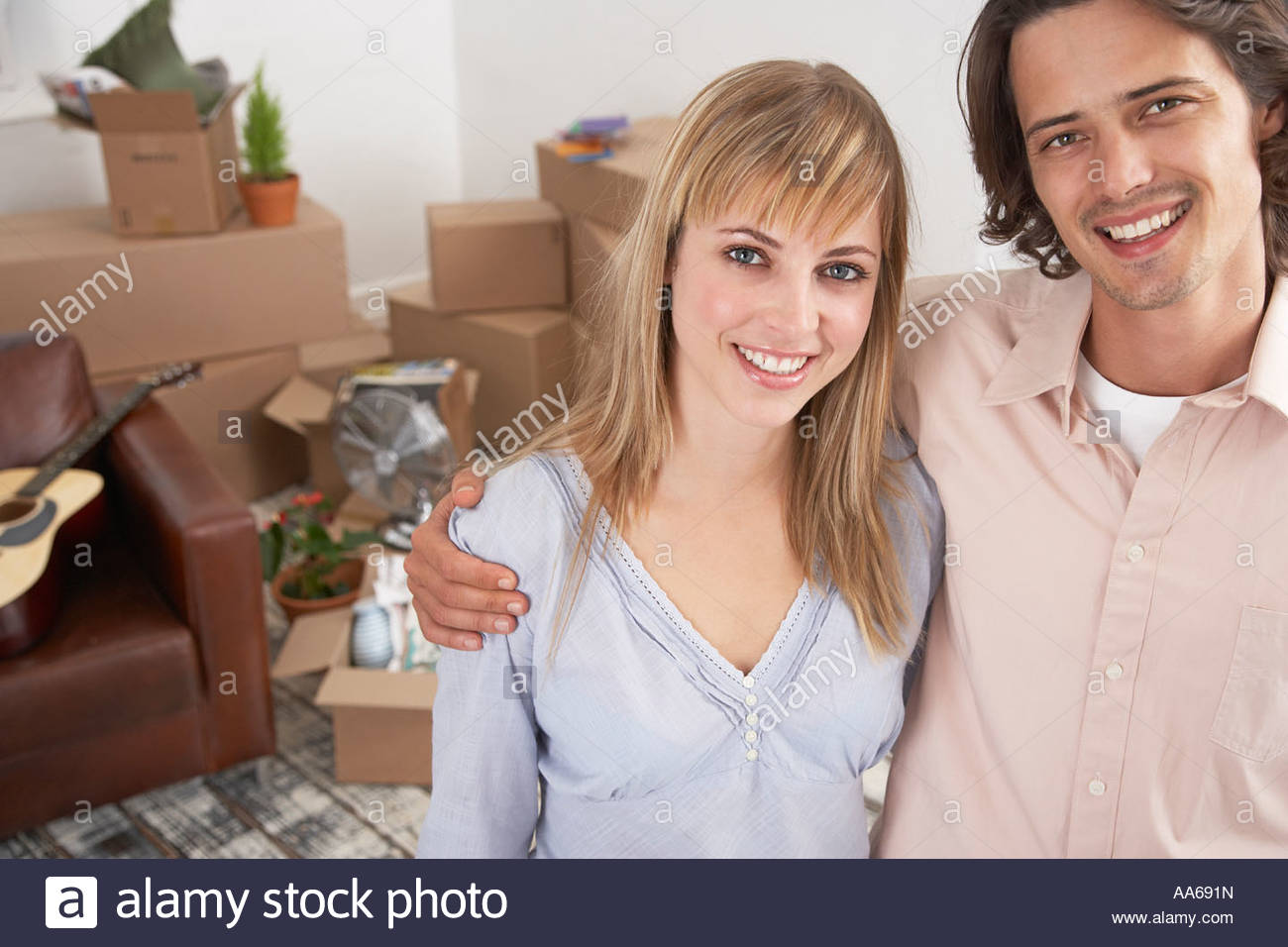 Man and woman in home with cardboard boxes and guitar smiling - Stock Image