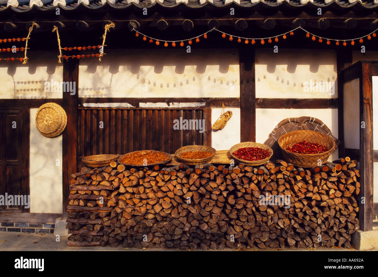Side of traditional Korean house with chillies drying on pile of logs Hanguk Minsok Chon Gyeonggi do - Stock Image