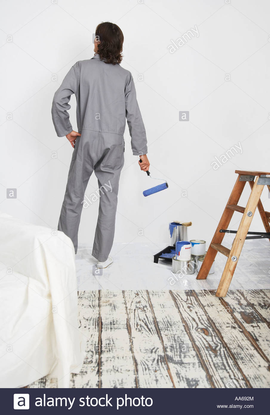 Man with paint roller looking at white wall - Stock Image