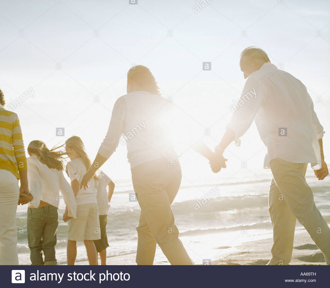 Couple  parents and children walking on a beach - Stock Image