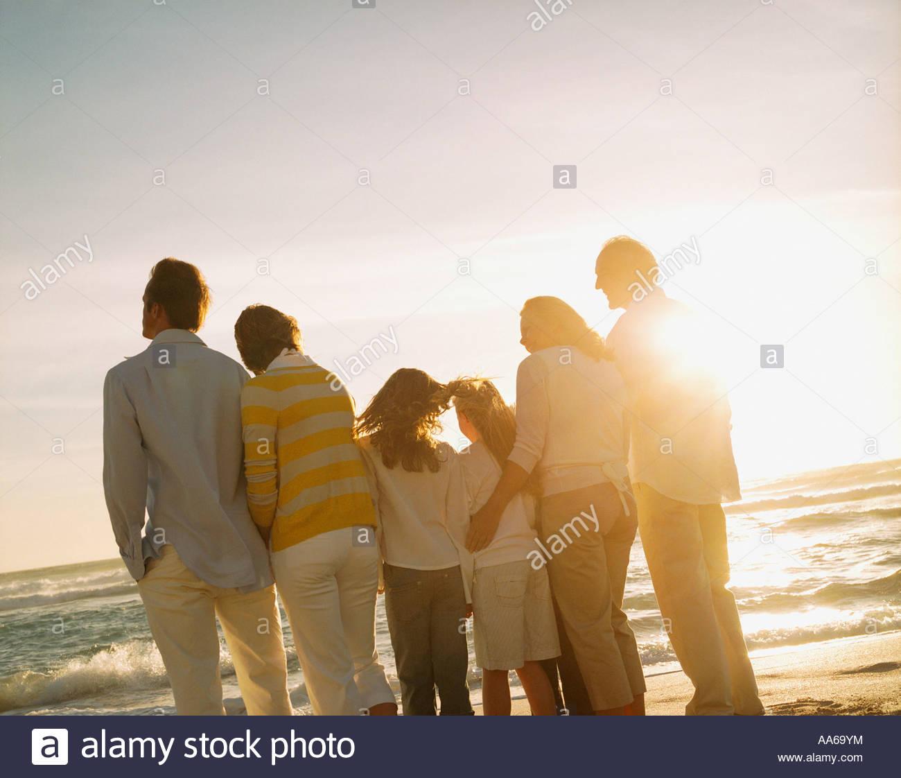 Multigenerational family portrait outdoors at sunset - Stock Image