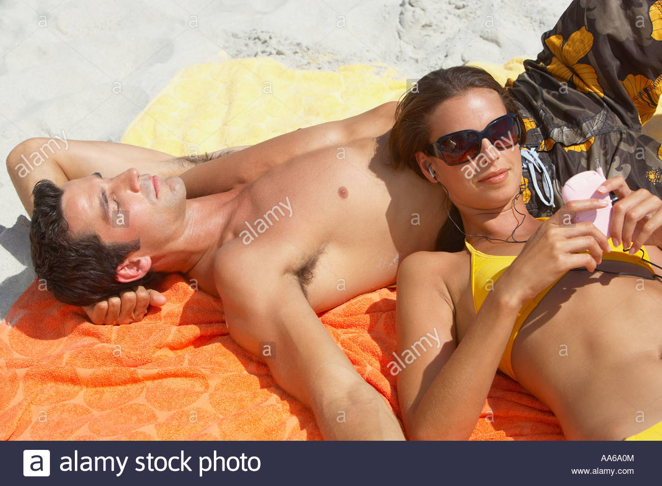 Woman in bikini with MP3 player lying down on man - Stock Image