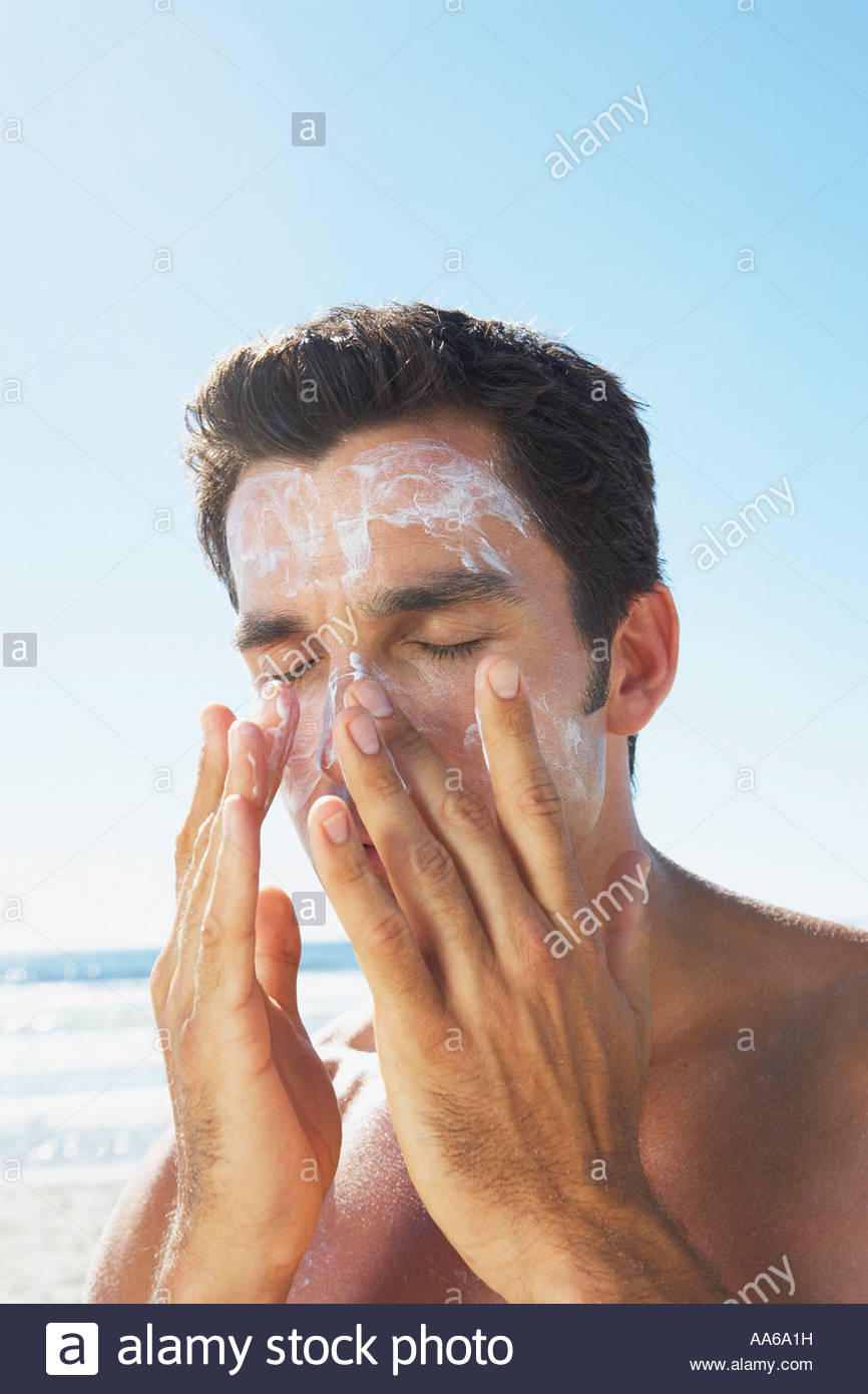 Man applying sun block or suntan lotion to face - Stock Image