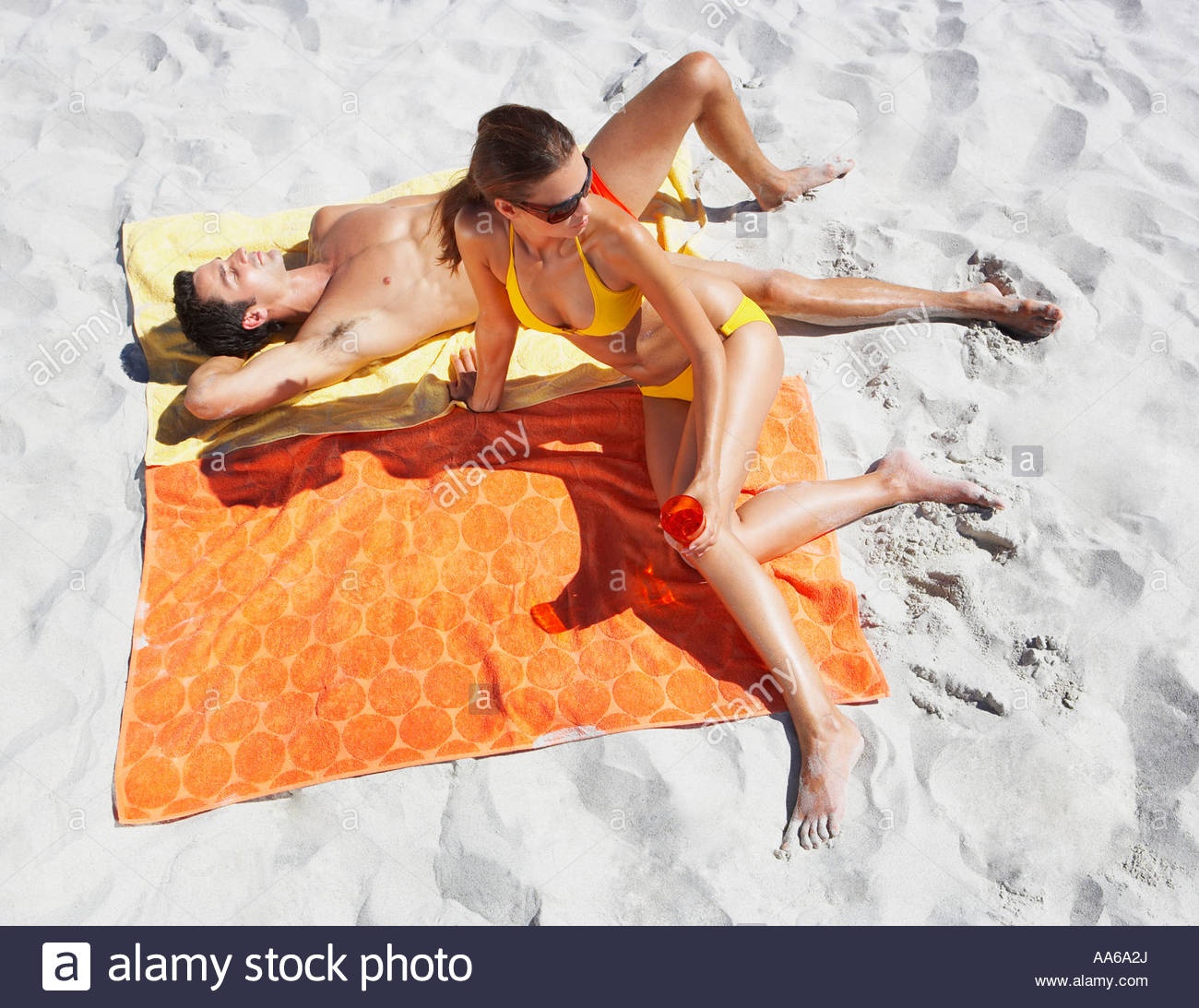Man and woman sunbathing on beach towels in sand - Stock Image