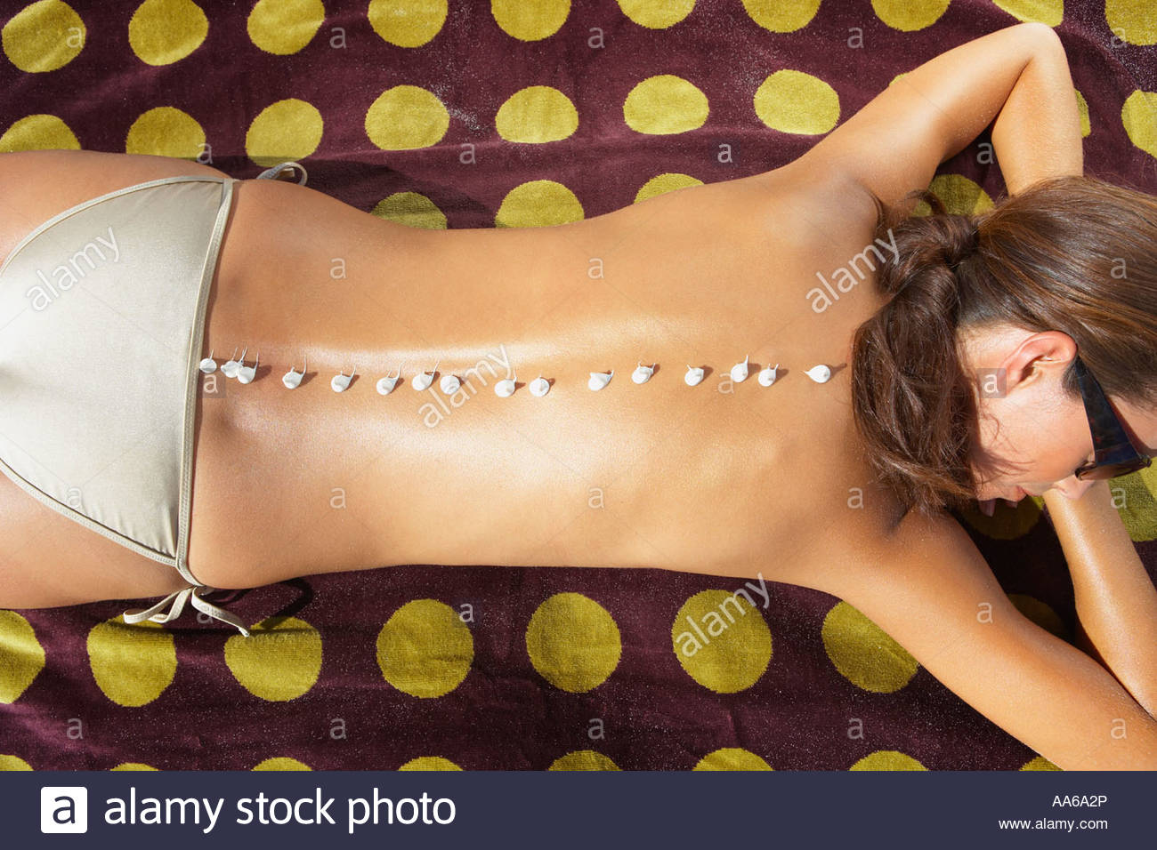 Woman lying down on beach towel with suntan lotion on back - Stock Image