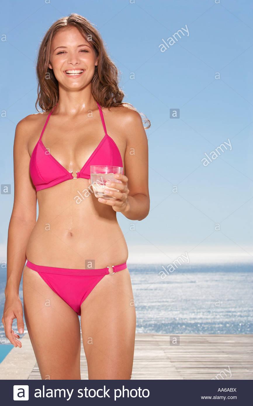 Woman in bikini with beverage outdoors - Stock Image