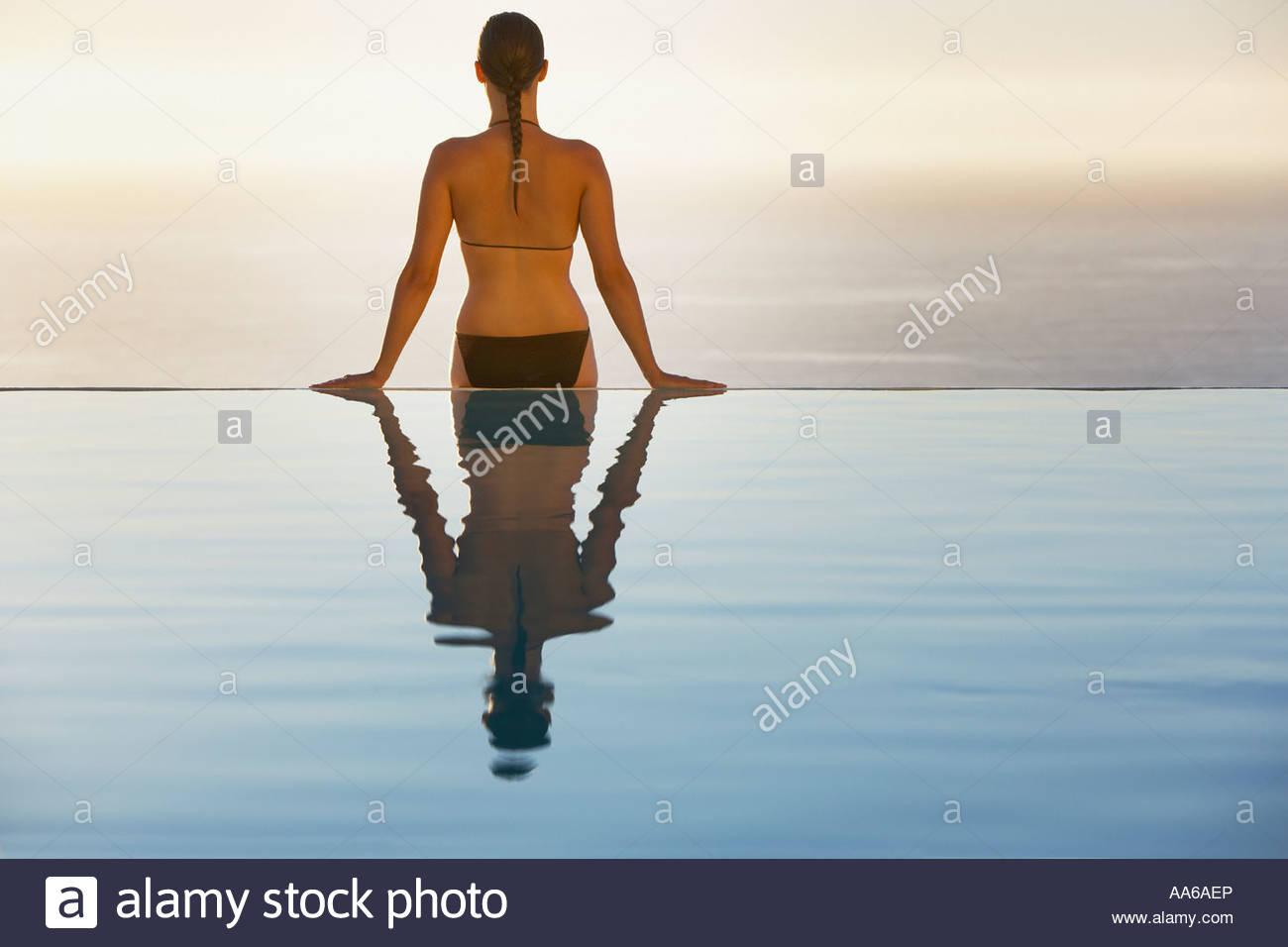 Woman sitting on edge of infinity pool in bikini - Stock Image