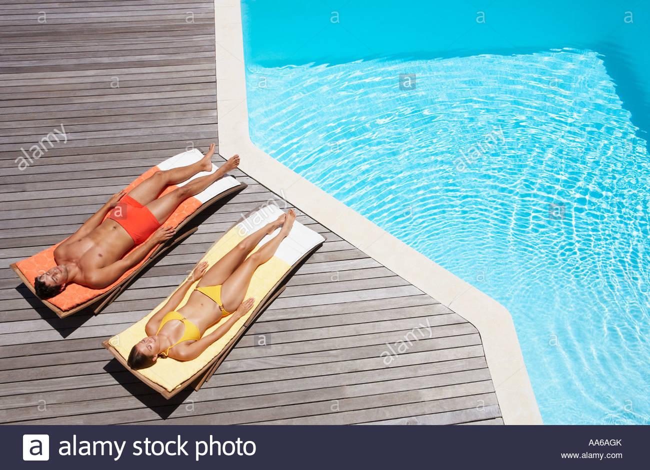Man and woman sunbathing on pool deck - Stock Image