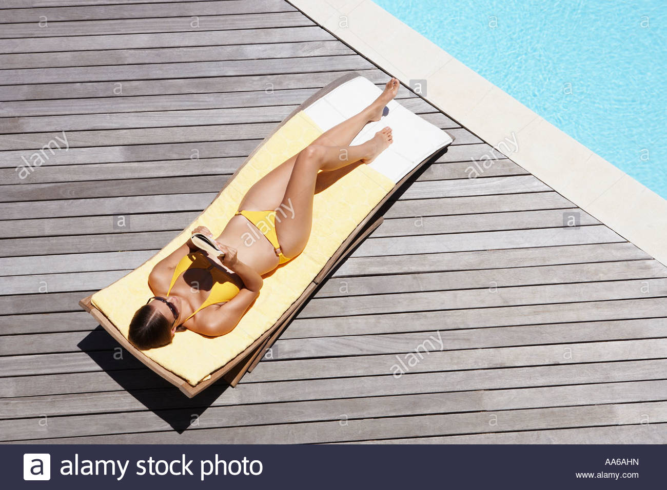 Woman sunbathing on deck outdoors with book - Stock Image
