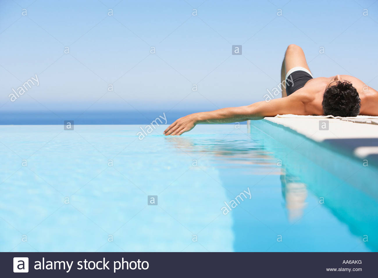 Man on infinity pool deck in swimsuit - Stock Image