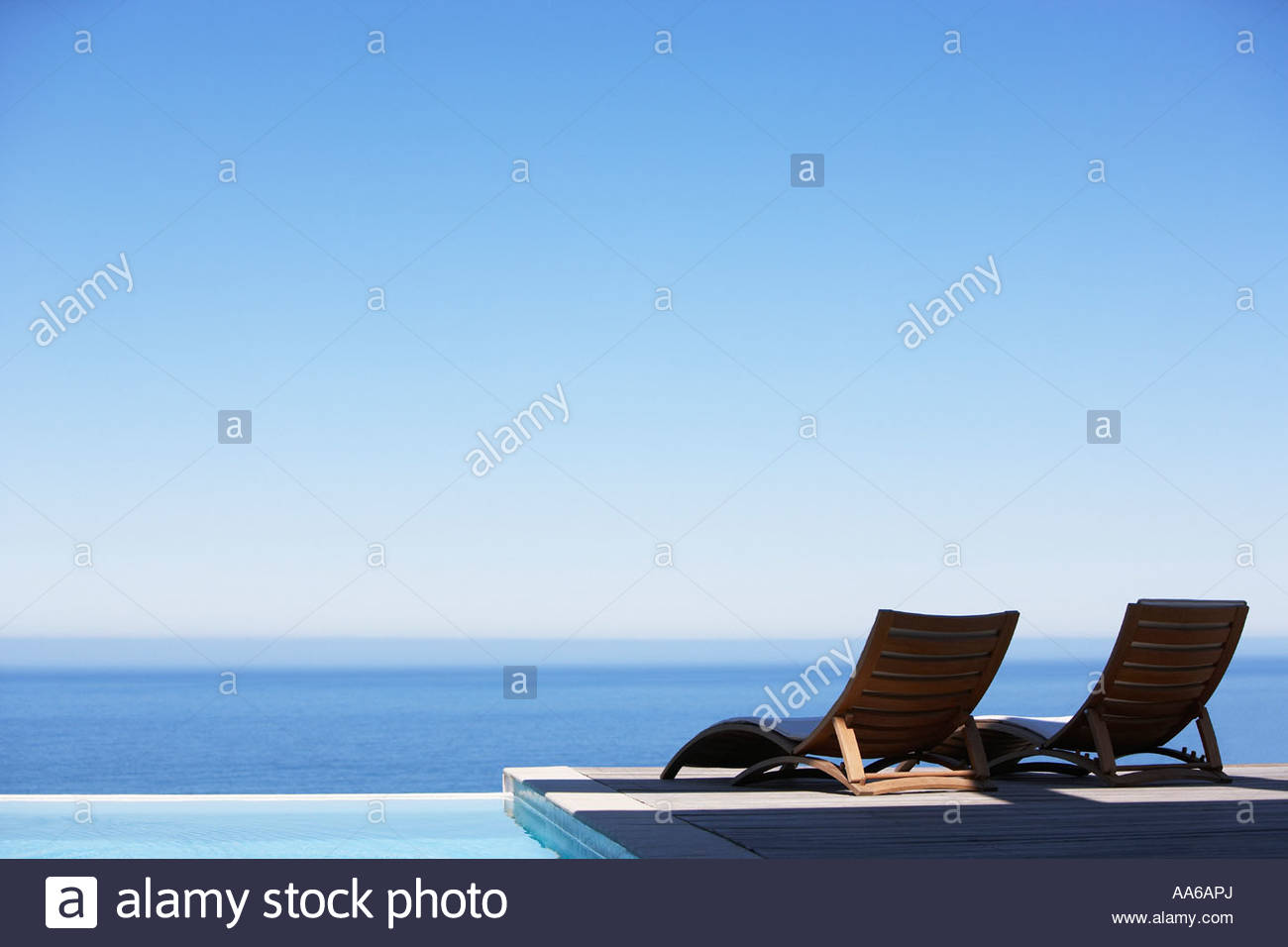 Folding chairs on infinity pool deck - Stock Image