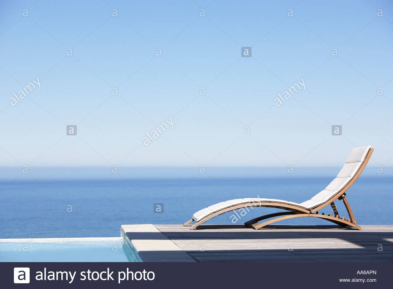 Folding chair on infinity pool deck - Stock Image