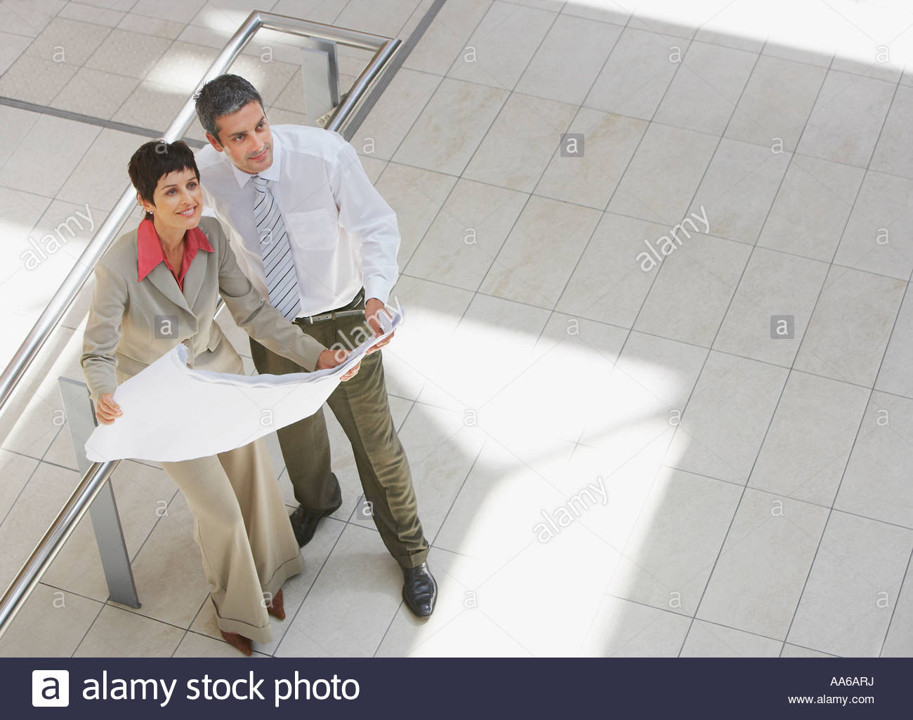 Aerial view of businessman and woman with blueprints - Stock Image