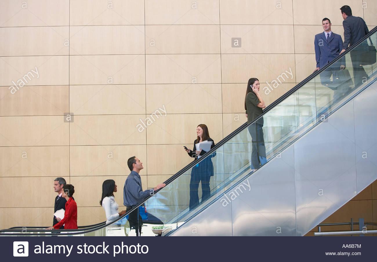 Businesspeople on escalator - Stock Image