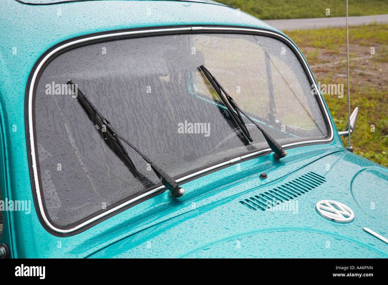 A VW Beetle standing in the rain - Stock Image