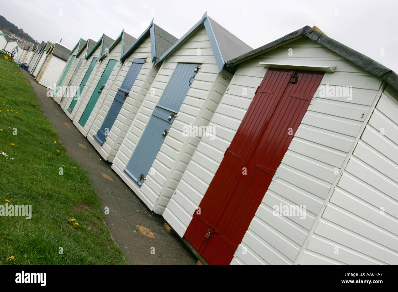 Brightly Coloured Victorian Beach Huts With Painted Doors Stand On