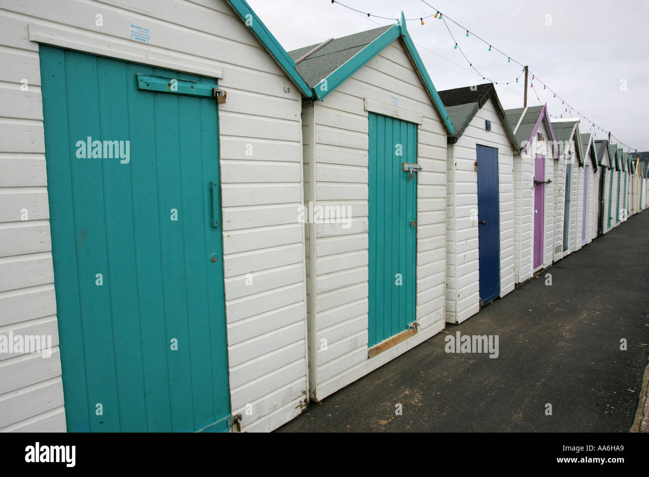 Long row line of white Victorian beach huts with brightly painted doors on Paignton seafront Devon England Britain & Long row line of white Victorian beach huts with brightly painted ...