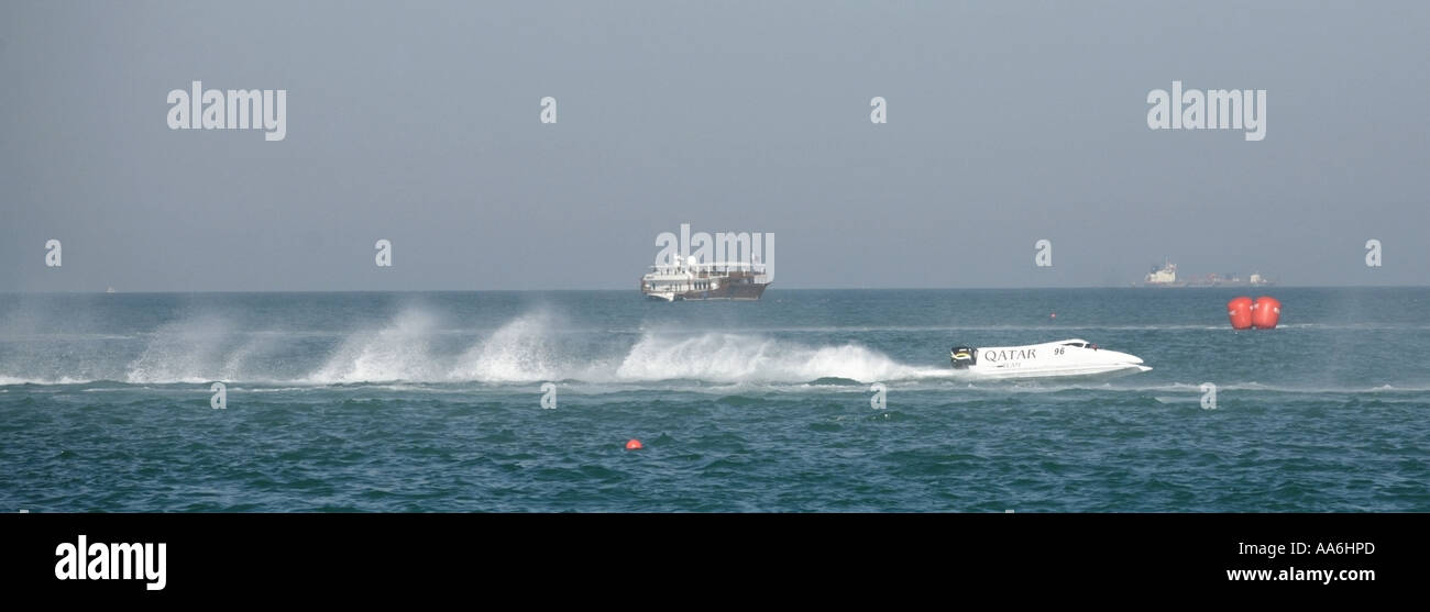 Mohamed al Ali's Team Qatar powerboat passes in front of a traditional dhow - Stock Image