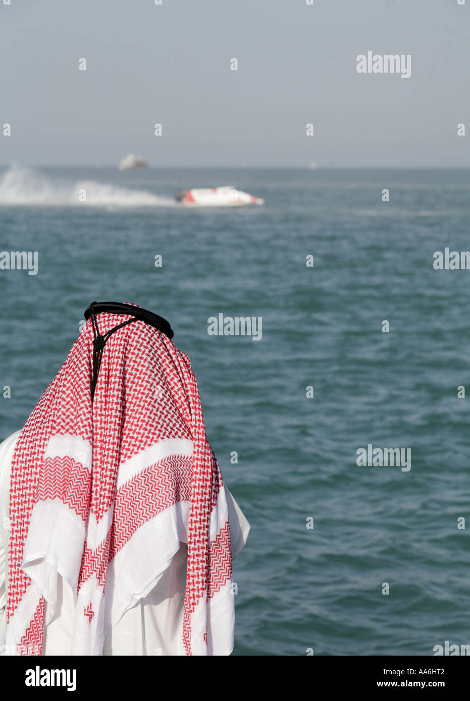 A Qatari in national dress watching the progress of the Formula One World Speedboat Championship - Stock Image