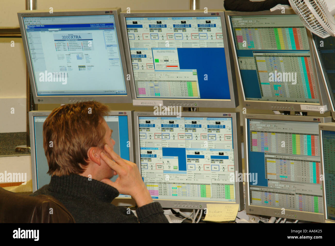 A male dealer in the financial markets in the City Of London is sitting at his desk looking at financial stocks and shares infor - Stock Image