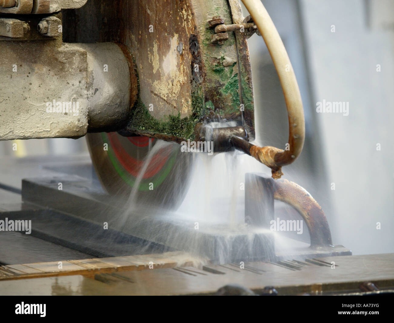 Industrial water cooled circular saw cutting a marble slab closeup - Stock Image