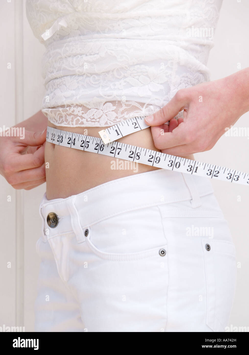 Slim girl measuring her waist with measuring tape white clothes caucasian vertical inches - Stock Image