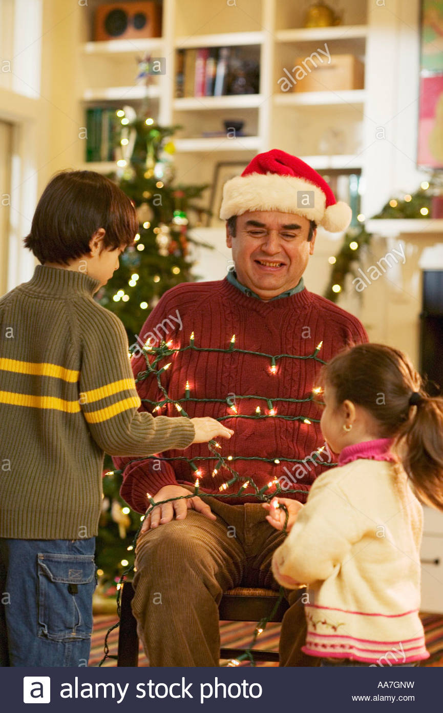 Children tying their father up in Christmas lights - Stock Image