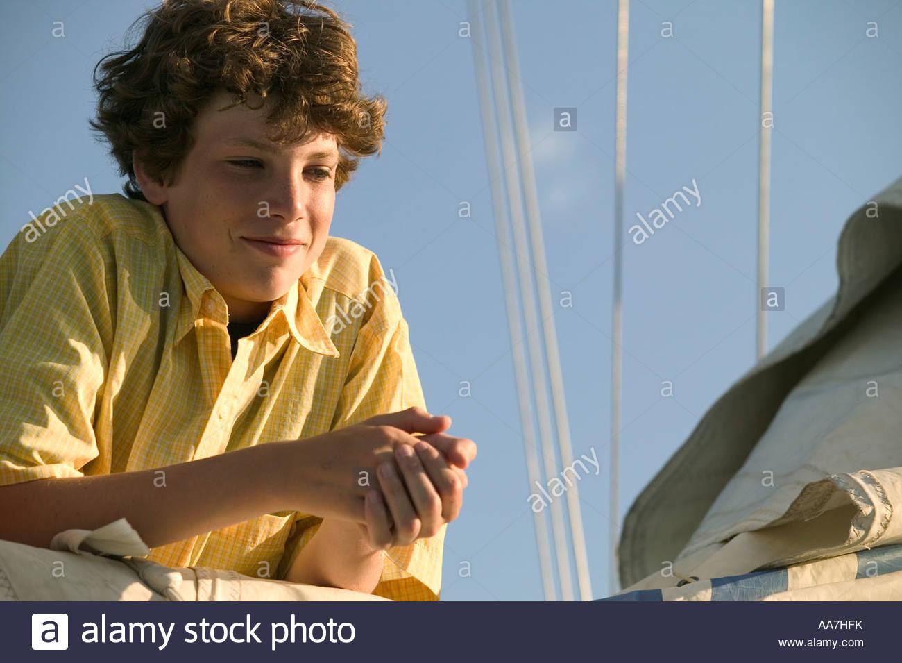 Teenage boy leaning on sail - Stock Image