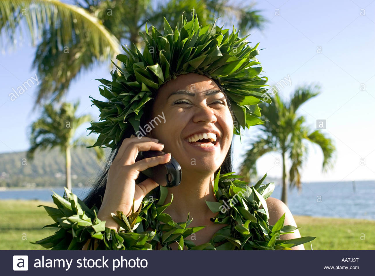 Hula dancer talking on her cell phone - Stock Image