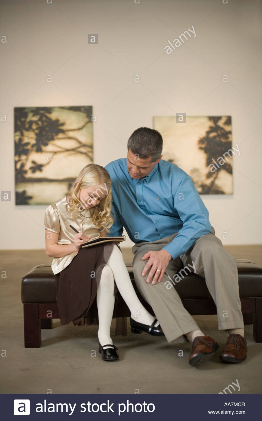 Father watching daughter sketch in art gallery - Stock Image