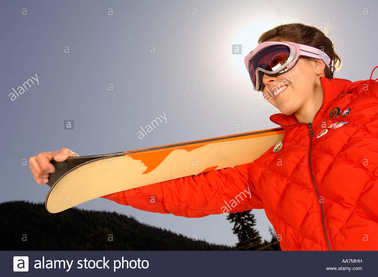 Female skier carrying skis - Stock Image
