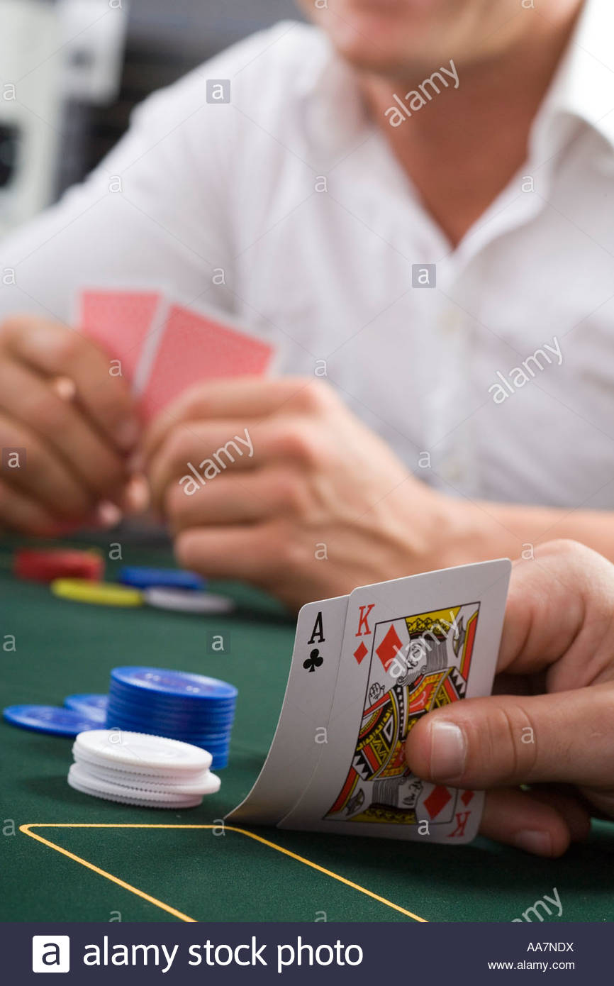 Close-up of cards on poker table, man in background - Stock Image