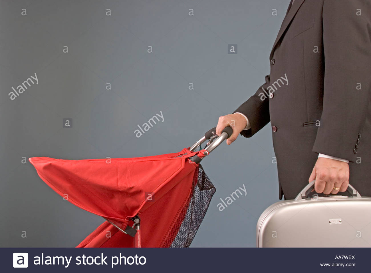 Businessman carrying briefcase and pushing baby carriage - Stock Image
