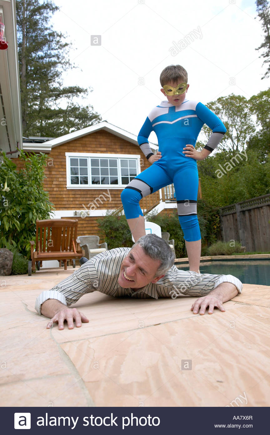 Young boy in superhero costume stepping on his father's back - Stock Image