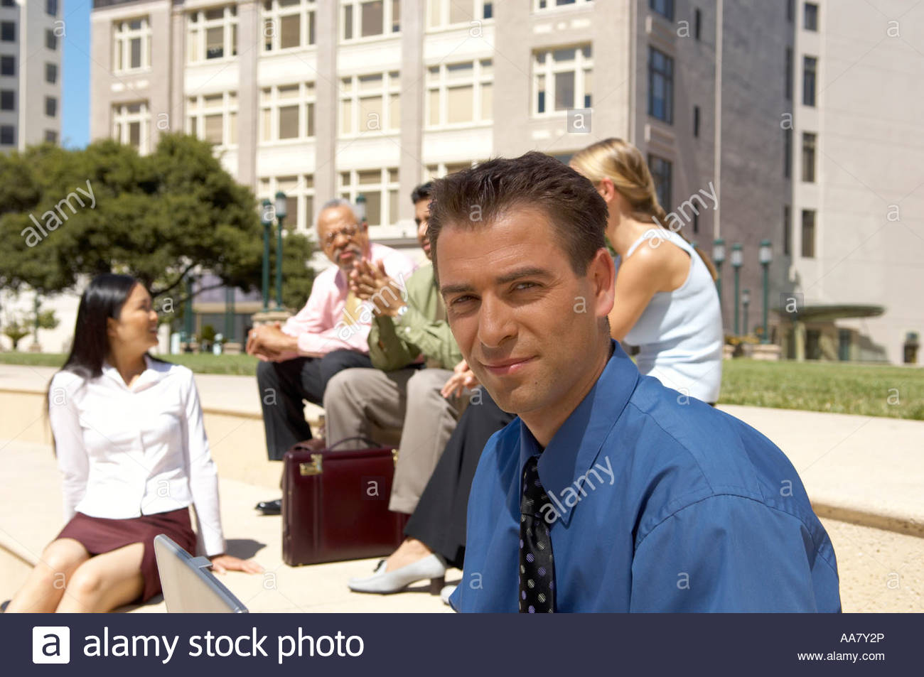 Businessman sitting separately from colleagues - Stock Image
