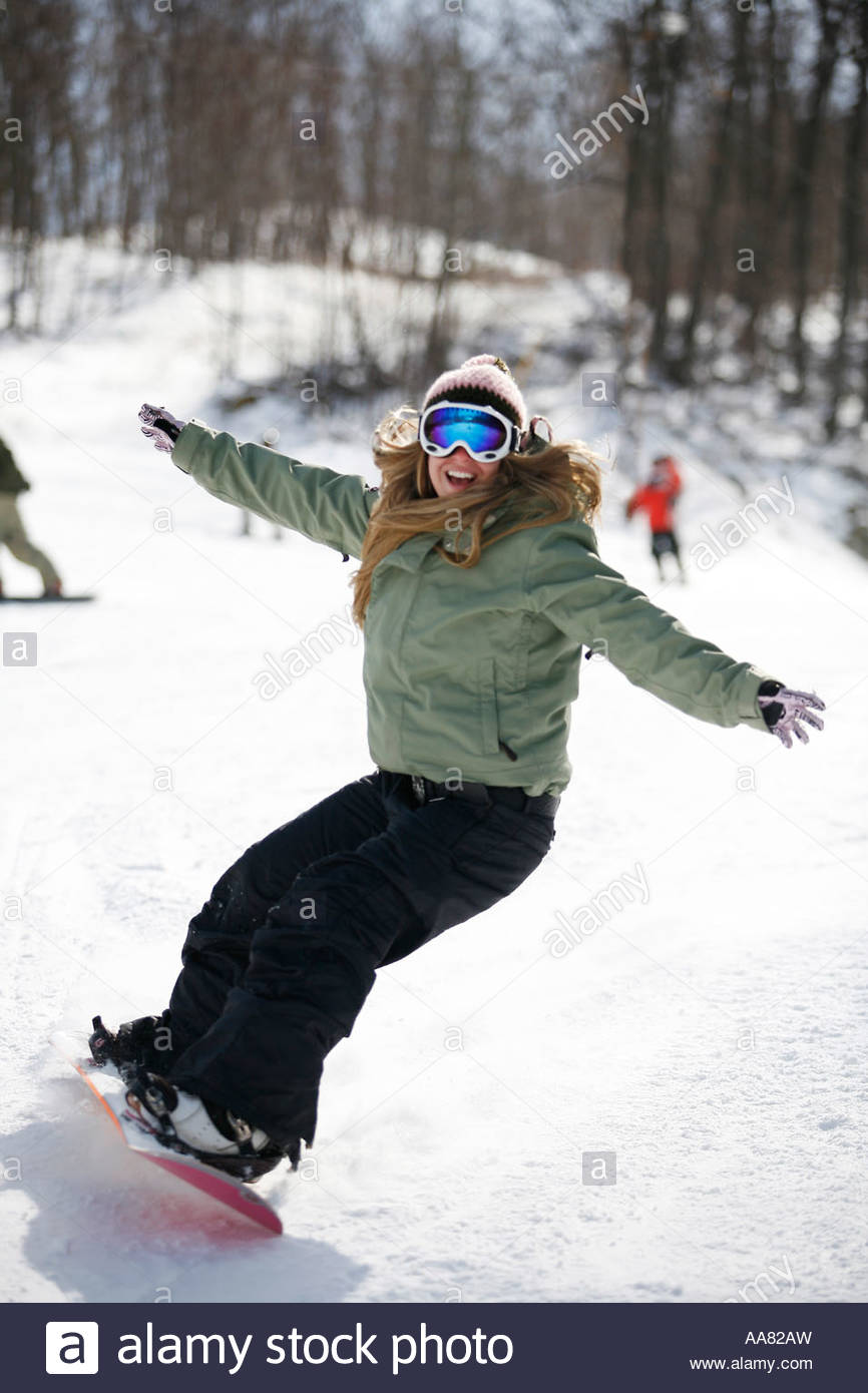 Woman snowboarding on ski slope - Stock Image